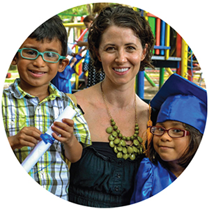 Woman with two children, one child wears a cap and gown