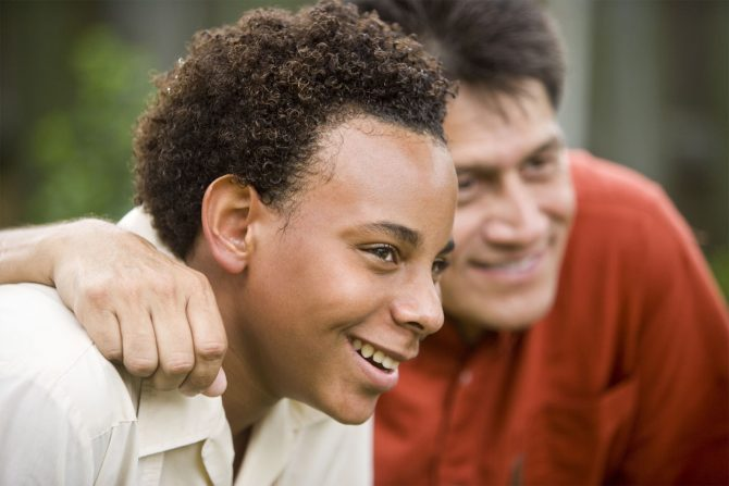 Man with his arm around a teenage boy